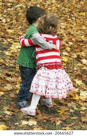 adorable toddler boy and girl hugging