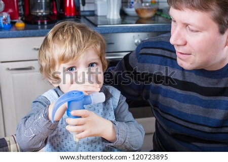 Adorable toddler boy and his father making inhalation with nebuliser, inhalator in home kitchen