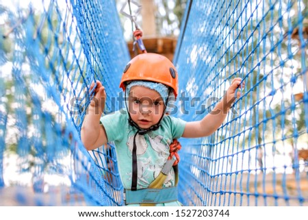 Adorable toddler boy having fun and enjoying her time in a rope playground structure at adventure park, outdoor family weekend activities, happy summertime, sport and active lifestyle