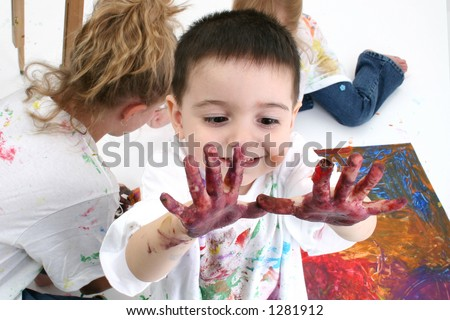 Adorable toddler boy looking at hands covered in paint.