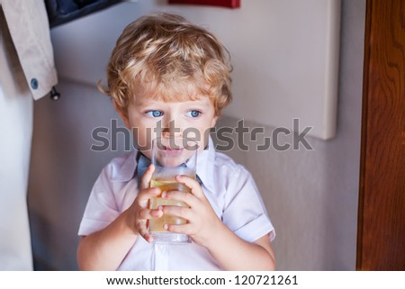 Adorable toddler boy with big blue eyes drinking apple juice