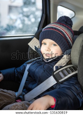 Adorable toddler boy with blue eyes in safety car seat