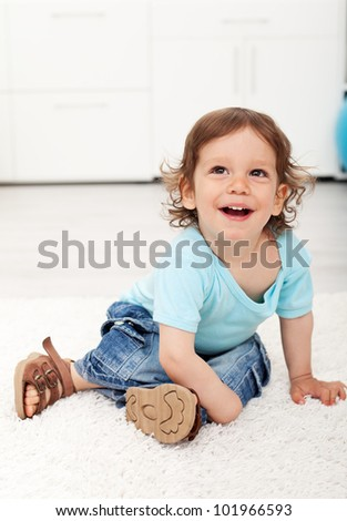 Adorable toddler child laughing on the floor - happy childhood concept