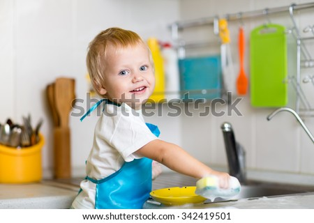 Adorable toddler child washing dishes in kitchen. Little boy having fun with helping to his mother with housework.