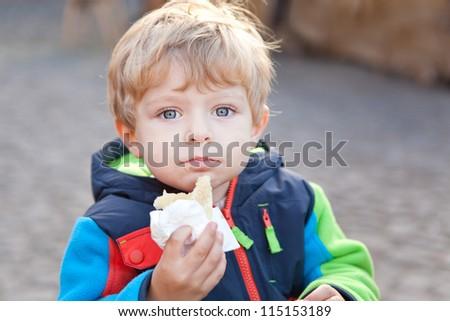 Adorable toddler eating bread outdoor autumn