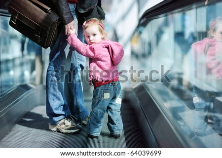 Adorable toddler girl and her father standing on moving escalator