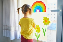 Adorable toddler girl attaching drawing of rainbow to window glass as sign of hope. Creative games for kids staying at home. Self isolation and quarantine concept
