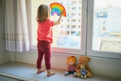 Adorable toddler girl attaching rainbow drawing to window glass as sign of hope. Creative games for kids staying at home during lockdown. Self isolation and coronavirus quarantine concept