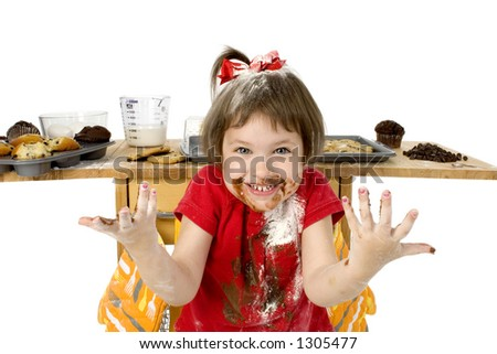 Adorable toddler girl covered in chocolate cake batter mix.
