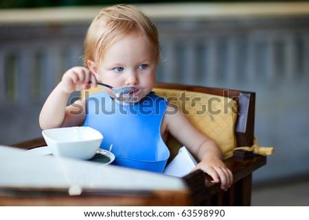Adorable toddler girl having breakfast
