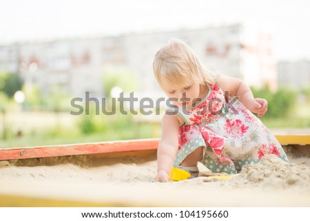 Adorable toddler girl in dress play with sand on sandbox