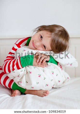 Adorable toddler girl in pajamas hugging her pillow