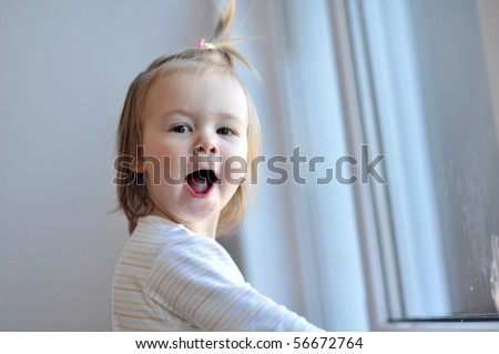 Adorable toddler girl looking  on the window