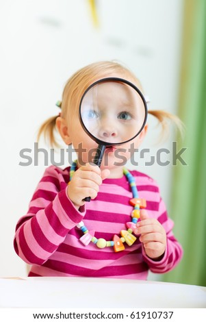 Adorable toddler girl looking through magnifier, perfect for early education context