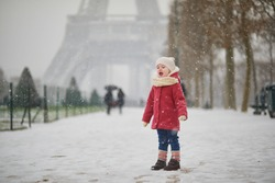 Adorable toddler girl near the Eiffel tower on a day with heavy snowfall in Paris, France. Happy child playing with snow. Winter activities for kids.