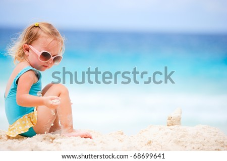 Adorable toddler girl playing on white sand beach