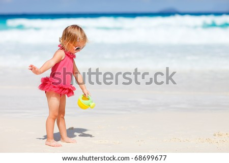 Adorable toddler girl playing with beach toys on white sand beach - stock photo