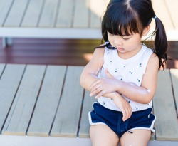Adorable toddler girl putting solar cream on arms hands Smiling happy outdoors by pool under sunshine on beautiful summer day.Mixed race Asian / Caucasian kid girl.Sunscreen or sunblock and Skincare.