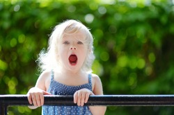 Adorable toddler girl screaming, singing and making funny faces outdoors at summer