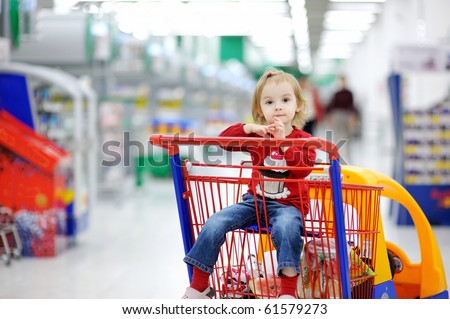 Adorable toddler girl sitting in shopping cart
