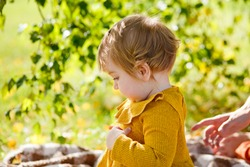 Adorable toddler girl sitting on the ground and having picnic in autumn park. Happy kid enjoying fall day. Outdoor activites for kids