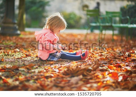 Adorable toddler girl sitting on the ground in Tuileries garden in Paris, France. Happy child enjoying warm and sunny fall day. Outdoor autumn activities for kids #1535720705
