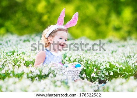 Adorable toddler girl wearing bunny ears playing with Easter eggs in a white basket sitting in a sunny garden with first white spring flowers