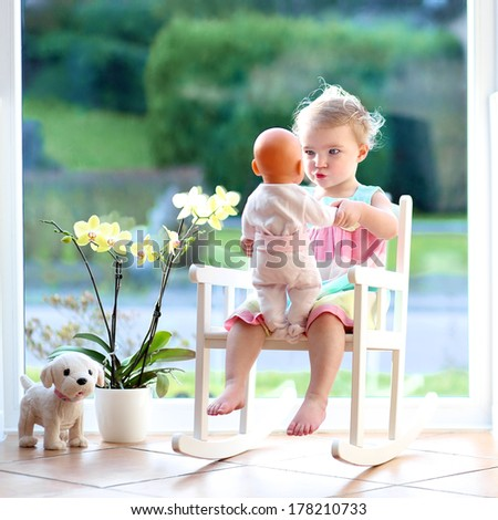 Adorable toddler girl with blond curly hair playing indoors with doll sitting on a rocking chair in white sunny room with big street view window