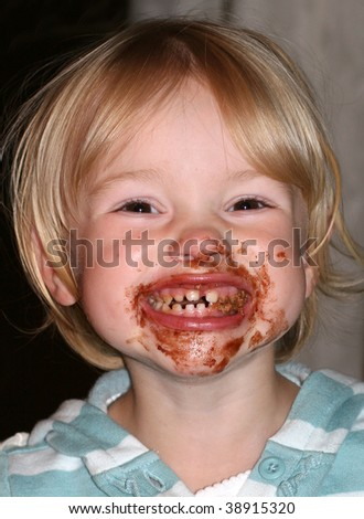 adorable toddler girl with chocolate all over mouth