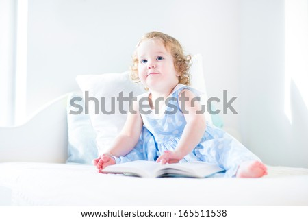 Adorable toddler girl with curly hair wearing a blue dress reading a book sitting on a white bed in a sunny bedroom