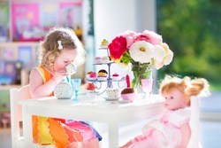 Adorable toddler girl with curly hair wearing a colorful dress on her birthday playing tea party with a doll, toy dishes, cup cakes and muffins in a sunny room with window