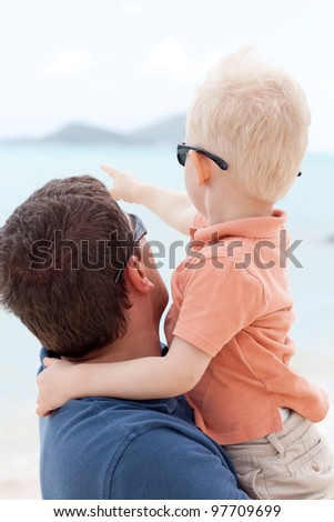 adorable toddler hugging his father and pointing the finger