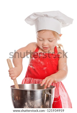 Adorable toddler in chef's hat and red apron stirring.  Isolated on white.