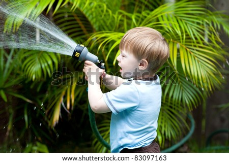 Adorable toddler watering plants in the back-yard - stock photo