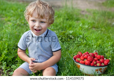 Adorable toddler with bowl strawberries on organic berry farm - stock photo