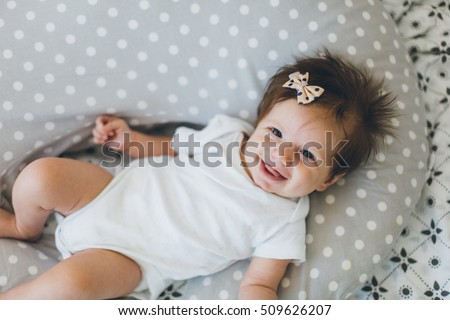 Adorable two month old  baby girl lying on the pillow and looking into the camera