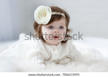 Adorable two month old baby girl lying on the pillow and looking into the camera. Portrait of a little baby on a soft blanket