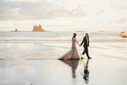Adorable wedding couple holds each other hands walking along the beach against the rocks and ocean waves in the evening light