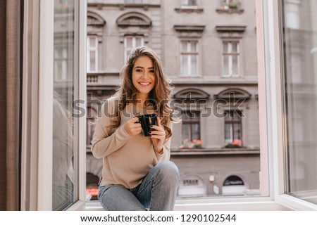 Adorable woman expressing positive emotions while posing on sill with cup of latte. Indoor photo of stunning female model with dark hair wears jeans and sitting beside window.