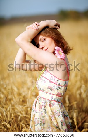 adorable woman in field with flower at summer sunset.