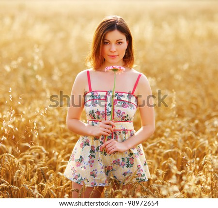 adorable woman in field with flower at summer sunset. - stock photo