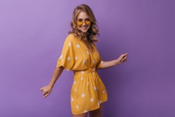 Adorable woman in vintage orange attire laughing to camera. Studio photo of spectacular girl with wavy blonde girl isolated on purple background.