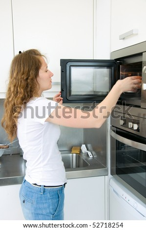 adorable woman is cooking by oven