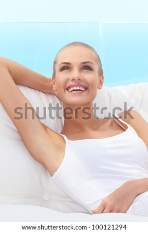 Adorable woman smiling broadly and looking off camera while seated on a white couch