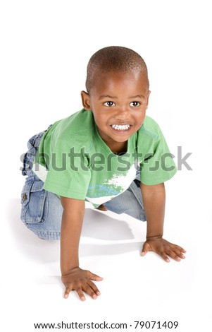 Adorable 3 year old african american or black boy on his knees smiling