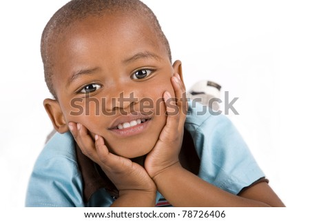 Adorable 3 year old black or African American boy laying with his hands on his chin smiling