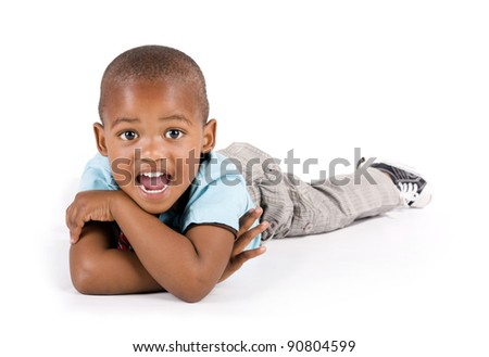 Adorable 3 year old black or African American boy lying on the floor looking very surprised