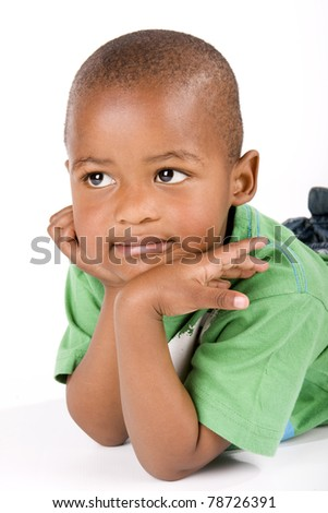 Adorable 3 year old black or African American boy lying on the floor staring into space