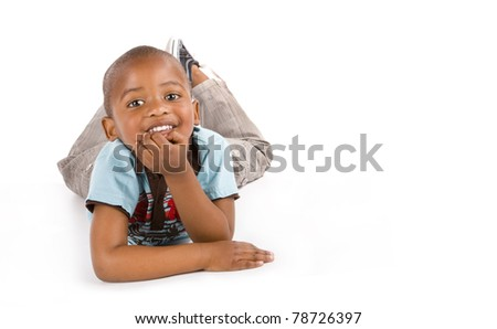 Adorable 3 year old black or African American boy with a big smile lying on the floor, space for your text.