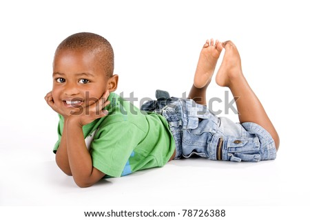 Adorable 3 year old black or African American boy with a big smile lying on the floor with his feet up looking at you